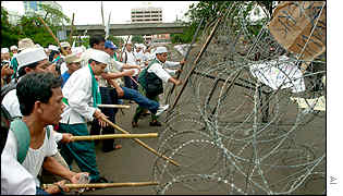 Muslim protesters use sticks to hit a barbed-wire barricade outside the US embassy.