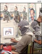 Palestinian militants with internet screens