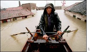 Man rows boat on flooded Yangtze AP