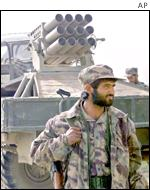 Afghan fighter in front of rocket launcher