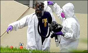 A fire fighter decontaminates an FBI agent at the AMI building in Florida