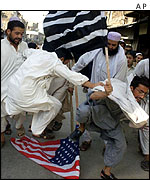 Taleban supporters stamp on an American flag in Peshawar