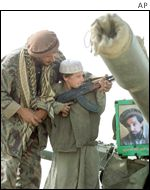 Fighter demonstrating a gun to young boy