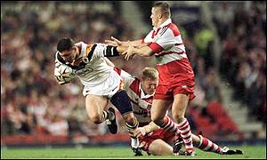 Henry Paul of Bradford is tackled by Neil Cowie of Wigan