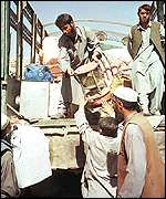 Afghans load their belongings on to a truck after their village was hit by an American bomb