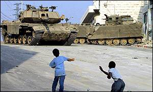 Palestinian children throw stones at Israeli tanks in Hebron