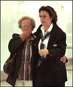 [ image: A distraught relative is comforted at Geneva airport]