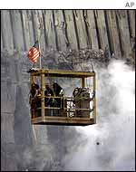 A crane lifts workers above the ruins of the World Trade Center