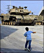 Palestinian child throws stones at an Israeli tank in Hebron