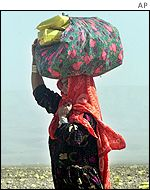 Woman carrying a shawl full of food packets