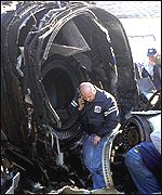 An American Airlines employee looks through the remains of one of the engines