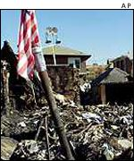 A flag flies over the wreckage of American Airlines flight 587