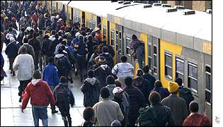South African commuters board a train