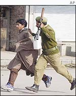 Indian soldier and demonstrator in Kashmir