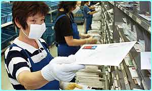 Postal workers handling mail in another country wearing protective gloves