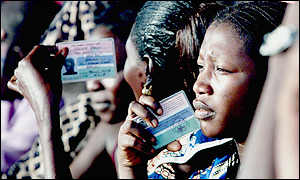 Voters in queue fanning themselves with ID cards