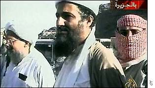 Osama Bin Laden (centre) with associate Ayman al-Zawahri (left)  and masked guard