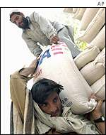 Workers load trucks with sacks of wheat