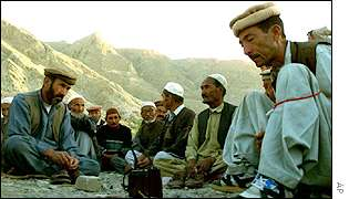 Refugees from Hazara community listen to the evening news in Pakistan
