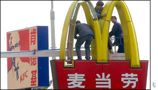 Chinese workers install lights on a giant McDonalds sign on the street of Beijing