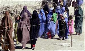 Afghan women refugees carrying their children enters into Pakistan at Chaman border post