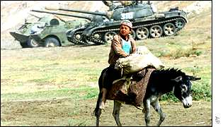 Child rides a donkey in front of a tank