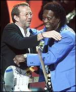 Eric Clapton and Buddy Guy hug after performing