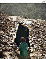 An Afghan woman and her child cross a steep mountain pass south-west of Peshawar