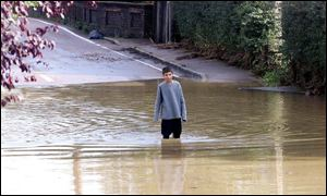 A young boy walks in the flood water in the village of Bocking near Braintree, Essex