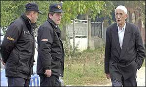 An ethnic Albanian man walks by two Macedonian policemen in the village of Tearce