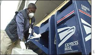 Postal worker in Detroit wears a mask and gloves to collect mail
