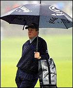 Scotland's Colin Montgomerie shelters from the rain on the 18th