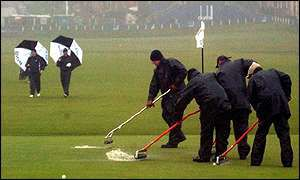 Green staff struggle to get surface water off the 18th