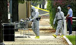 Workmen in biohazard suits push equipment into a Congress building in Washington
