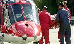 Paramedics carry a casualty into a rescue helicopter at the southern portal of the tunnel