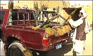 Taleban fighter loads rocket propelled grenades onto a truck
