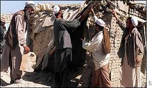 Afghan residents on the outskirts of Kabul inspect a damaged house