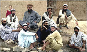 Afghan tribesmen listening to a radio