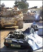 Squashed car and Israeli tanks in Beit Rima