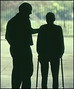 Silhouette of an elderly person being helped