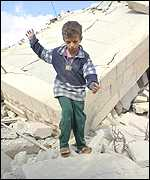 A Palestinian boy plays on the ruins of a house destroyed by Israeli soldiers