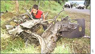 A boy looks at the wreckage of a car bomb