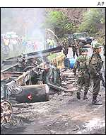 Colombian soldiers with remains of burned tanker truck
