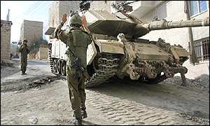 An Israeli soldier directing a tank in Bethlehem's narrow streets