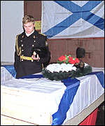 Sailor stands by coffin