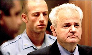 Slobodan Milosevic arrives in court flanked by guards