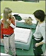 Two girls chat in their shared bedroom