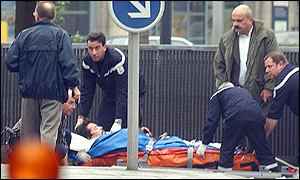 Police secure the gunman on a stretcher