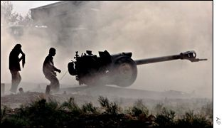Northern Alliance troops fire a howitzer