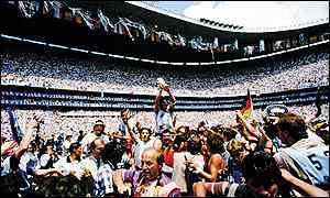 Maradona raises the World Cup trophy as he is carried along by the crowd